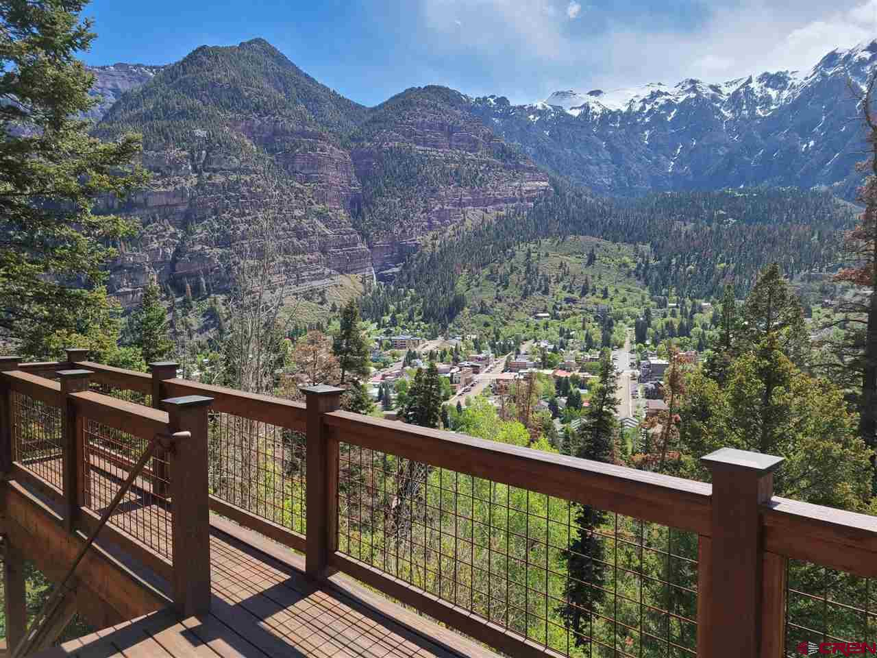The most fabulous views above Ouray and complete privacy! 4 acres bordering National Forest on two sides with a 6.4 acre green belt below the home. Walk inside to luxury! 3 bedrooms, one with bunks, 4 full bathrooms, stone fireplace with crystals, deck looking out over Ouray and surrounding mountains, hot tub on lower patio, and a charming gas firepit on the side of the hill. Comes completely furnished - bring your toothbrush.  Stunning views in all directions are yours from this unique property! This three bedroom, four full bath home was completely renovated in 2010 with high end finishes and custom furniture throughout. The original wood burning fireplace remains and is constructed using local stones, geodes and crystals. The home is being sold completely furnished.   Stone patios surround the home and extend behind the house to an outdoor seating area with a gas fire pit and more incredible views. The large hot tub in front of the home has impressive views to the town below and the mountains beyond where you often see the alpenglow at sunset.  Windows are present in every room and bathroom of the home to take in natural light and to enjoy the views from every location. A new deck was installed in 2018 that provides for easy outdoor entertaining or just relaxing with family and friends.   The home sits on 4 acres and is protected on all sides for complete privacy. Oak Creek forms the southern boundary, national forest surrounds it to the west and north, and the east side is adjacent to a 6.4 acre green belt conservation easement between the home and the town of Ouray. A controlling interest in the green belt is also included in the price of this home. One of the access points to the Ouray Perimeter Trail is located on the greenbelt, just a few minutes walk from your front door. While you are still within walking distance to the town of Ouray and all that it offers, the home is located in the county and is not subject to city property taxes. This property is a rar