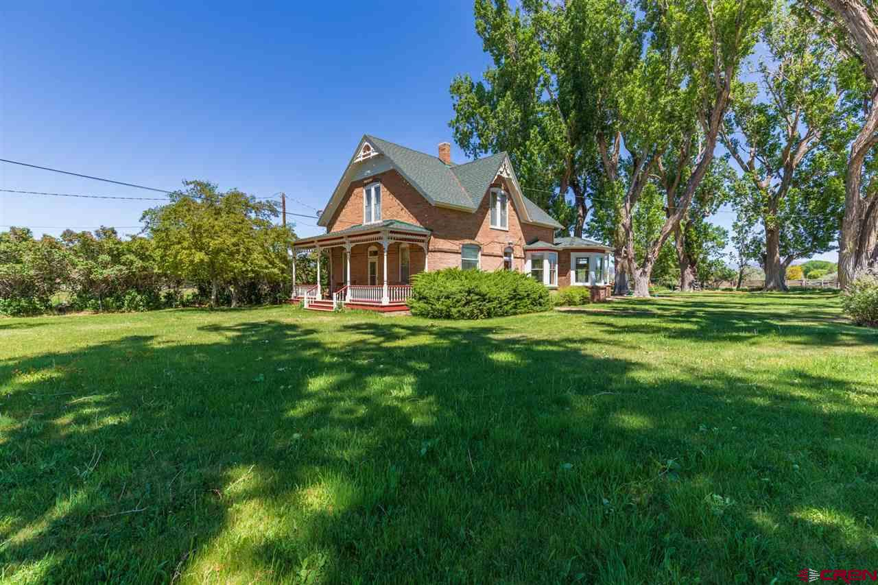 The Baker Ranch - located off 6250 Road on Spring Creek Mesa. This picturesque 26+ acre ranch has been lovingly care for - for 50 years by the Baker's. Featuring a 2-story brick, Victorian style home w/all the charm of that era. Formal living room w/den, formal dining room w/built-ins and bay window, updated kitchen w/absolutely charming breakfast nook w/views from the bay windows, and master bedroom/bath - all on the main level. Upstairs includes 2 large bedrooms w/transom windows above the doors, a second den and a beautifully updated 3/4 bath. Outdoor spaces include the front porch - perfect for your rocking chairs - and a wonderful screened in back porch that opens onto a large deck w/the beautiful old cottonwoods for shade. The old red barn and several sheds stand ready for use. The irrigated acreage is in grass hay and offers non-stop views of the surrounding mountains. Bring your kids, bring your dogs, bring your horses (cows, sheep & chickens!) - BRING YOURSELVES to this beautiful Spring Creek oasis.