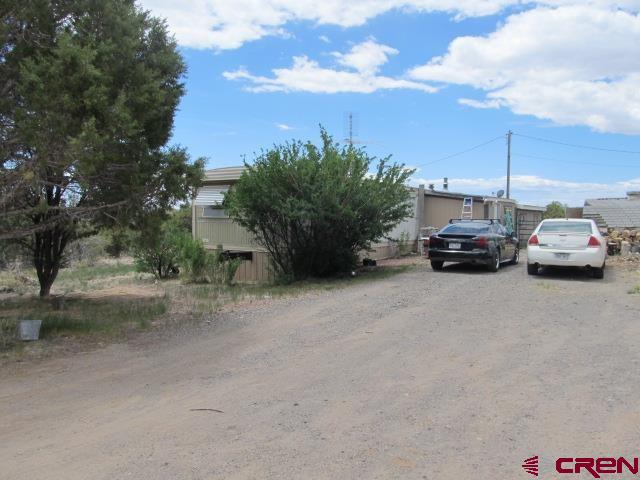 This property has a lot to offer.  2 pre-hud mobile homes on 4.67 acres are what is obvious.  What you might overlook is the oversized garage/shop that contains a car lift and has an air compressor and piped air throughout.  Take a walk to the upper end of the property and enjoy endless views of the grand mesa or gaze south to unobstructed views of the Uncompagre plateau or San Juan mountains.  The bottom part of the property has wonderful trees that have been cleaned up to help with fire mitigation and has a seasonal lateral ditch to enjoy the cool sounds of water through the property.  This property has so much potential, with water being short this year this property has two, Yes TWO domestic water taps.  The two mobile homes are very livable and could lead to many possibilities.  Live in one and build a home?  Live in one and rent the other?  This is a great property for someone that has a vision or simply someone who likes what is completed already.  Measurements and most information pertains to the 1974 Buddy Size 14 x 70 mobile home.  The 2nd home is a 2 bedroom, 1973 Columbia Size: 14 x 65 mobile.  The main home has a dishwasher, the 2nd home does not.  Each home is on its own electric meter.