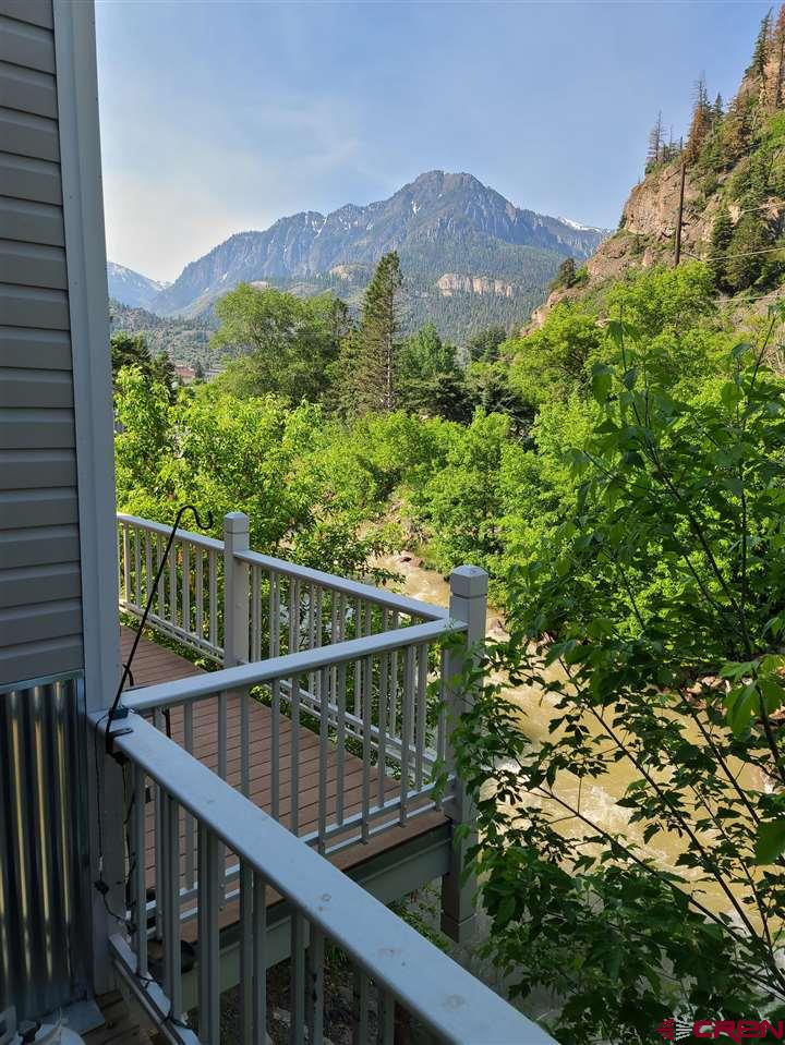 Wonderful property next to the Ouray Hotsprings Pool. Nice mountain views out the windows and over the awesome deck that sits over the Uncompahgre river. Convenient walk to town or cross Main Street to the catch the perimeter trail. 1,200 square feet with an attached garage. In 2020 new windows and laminate flooring were installed and the kitchen got new appliances. New tub surround is being installed in the upstairs bathroom. Pellet stove for cozy warmth and ambiance. The homes in this complex have historically been both short term vacation rentals and full time residences. Make it yours today!
