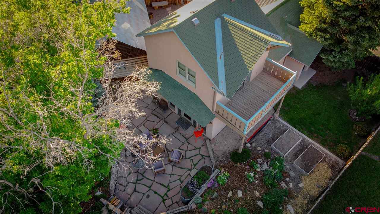Charming home in the Town of Ridgway is within walking distance to restaurants and shopping. This quiet location offers spectacular views of the Cimarron Ridge in the San Juan Mountains of the Colorado Rockies. Fenced yard around the house allows for the beautiful landscaped gardens and extra privacy. The main home has forced air, and in floor heating. New appliances are washer/dryer and refrigerator/freezer. Kitchen has a Thor propane range for the chefs that like to cook. Amazing stained glass adds to the character along with big windows and skylights. The 245 square foot cabin in the back yard has potential for various uses including a covered porch with 220 power. Lots of parking in the back drive. Workshop has power, and wired with lighting. Large greenhouse is a plus. Property has mature trees, lots of grass, and heavily treed mountain in the back.