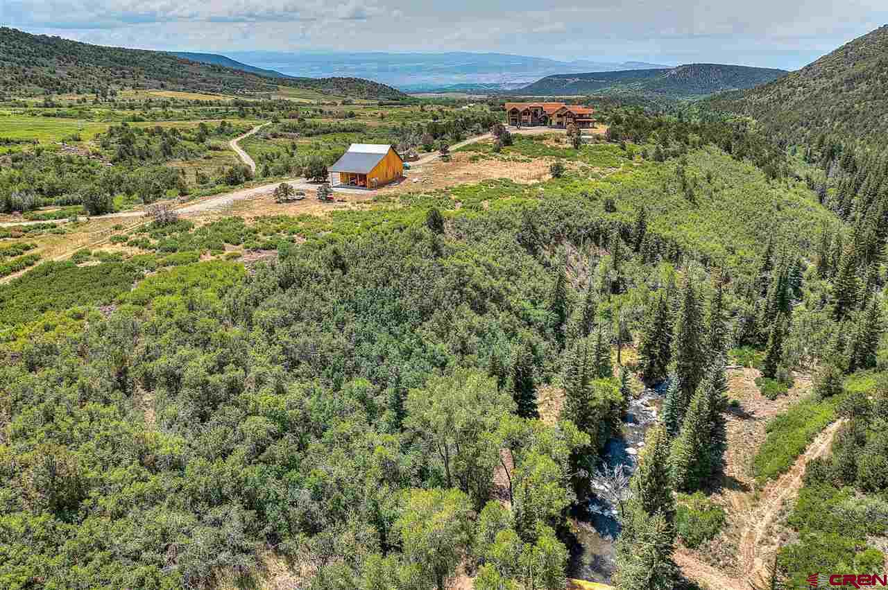 This Leroux Creek Ranch is a distinctive offering located on 1700 +/- acres in the quiet mountain town of Hotchkiss Colorado near the Grand Mesa National Forest. This extraordinary property's anchor is an 11,000 square foot lodge that rests high above the neighboring valleys and is seen and admired from miles around. With 10-bedroom suites and 11 bathrooms, the lodge is versatile and can be used as a luxury home, an exceptional hunting property, or for destination events or corporate retreats.   The property is teaming with wildlife. Deer, bear, elk, turkey, and mountain lions call home to this land, and the streams are packed with trout and other native fish. The owners of this property have been diligent in clearing areas and providing water tanks up and down the mountains to enhance the wildlife habitat. With the 10 +/- miles of private roads and trails that wind through the property, you'll spot an assortment of wildlife as you pass over the gushing waters of the Leroux and Cow Creeks and make your way up into the oak brush and then further up into the sprawling aspens. From the ridge top, you'll see the surrounding town, cattle ranches and have a birds-eye view of the stunning lodge.    The Lodge has a stamped concrete driveway, adorned with flagstone accents, leads to a massive and striking all-glass front entry. Stepping inside, you're greeted with modern rustic lighting and exposed log beams with an expanse of windows that stretch the length of the great room. During the day, those windows provide spectacular views of the mountains, and at night, the stars drop so close, they seem to fall into the room. The constellations appear as bright and clear as in a planetarium.  The open floor plan allows people to gather together in the large areas or retreat to their own private suites. One of the many design features of the property is that there are specific and extraordinary views from every window and angle.   The kitchen is large and professionally equipped wi