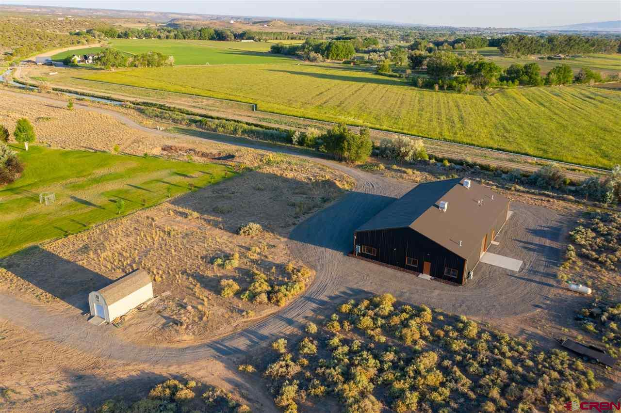 """Opportunity awaits....here's your chance to own a little slice of heaven right here on the beautiful western slope of Colorado. Situated on 1.5 acres, This 6000 square feet of space does not disappoint. A """"barndominium"""" of sorts, LIVE & WORK with 5000 square feet of """"shop"""" space,  FIVE Garage bays (all different heights and lengths), 220 Amp Outlets for welding/lifts, two """"Reznor"""" area space heaters, & two swamp coolers; the possibilities are endless!! With just under 1000 square feet, the living space is quite lovely indeed; including three bedrooms (two of them non-conforming), small living room & a kitchen. It comes with instant hot water heat including a tap outside so keeping the cars and toys clean year round is never an issue. The VIEWS are tremendous; sunrise & sunsets could very well be nothing like you've seen before. Take advantage while it is available, THIS ONE IS A GEM! ** There will be a Chipeta water tap included in the sale price.  ** Please take the opportunity to walk through this property virtually in 3-D. simply click the links under branded/non-branded virtual tours."""