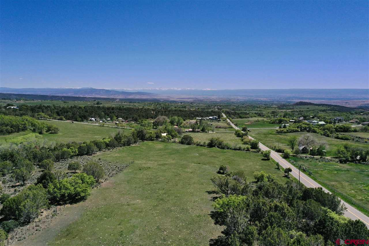 Amazing piece of property with varied terrain and spectacular San Juan and Grand Mesa views! Tucked up at the base of the Grand Mesa, this parcel has multiple meadows, mature vegetation, and a number of excellent building sites. With rambling meadows and slight ravines, this property is also a wildlife paradise. One corner of the property borders Highway 65, and is absolute prime frontage for advertising to the public as they pass by coming and going from the Grand Mesa. The property is being conveyed with 1 share of Surface Creek irrigation water. There is currently no domestic water tap, but when they become available through Orchard City domestic water a new owner could purchase one. Don't miss out on all that this piece has to offer! *PLEASE do not open any gates as there are currently cattle on the property*