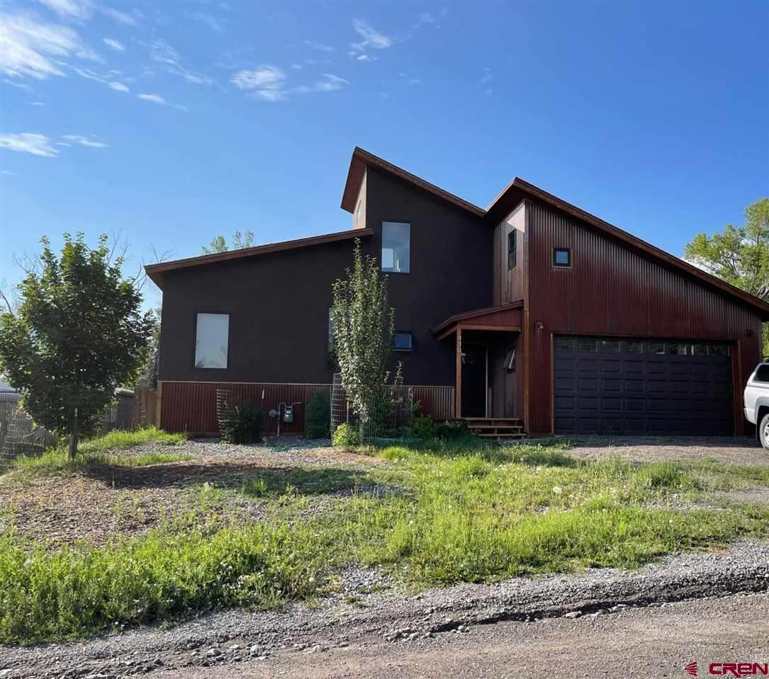 DON'T MISS THIS ONE IN RIDGWAY!!  This is an incredible opportunity to own a Modern 2015 3 Bedroom/3 Bathroom home with a 1 Bedroom/1 Bathroom lock-off apartment.  Green energy built per Town of Ridgway regulations as well as passive solar. Located just minutes to the core of Town and all of its amenities.  Panoramic mountain views from the south facing deck.  Stick built with stucco and rusted metal exterior.  The main level consists of:  3 Bedrooms, 3 Baths, open floor plan that flows from kitchen to dining to living room.  Upstairs is accessed by a spiral staircase of a wall ladder.  This area of the home could be but are not limited to:  study, work out area, office, library, etc.  The lock-apartment is accessed through the garage and a stairwell.  It is a great use of space and could be used as a rental for extra income.  The main floor is heated with natural gas in floor radiant and the lock-off is heated with hot water baseboard.  The flooring is cork, slate and laminate.  Spacious 2-car garage and a modest shop in the back that has electrical service.