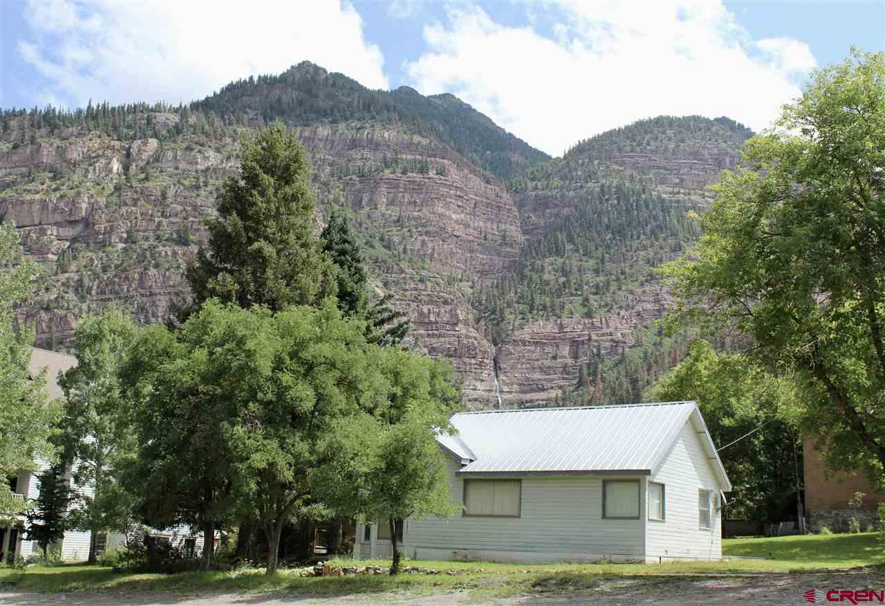 Great location, with views and a very large city lot! This home sits on a prime corner and comes with .29 acres which is a very large and rare lot for the city of Ouray. The assessor has the home as being built in 1914, but the owners have found proof the home was actually built in 1882 with additions added later on. The home has a great basement and foundation, with lots of potential to remodel and make this sweet property shine! With the R-2 zoning you could also build a multi unit complex with more than 10,000 sq ft per city code for this zone. The foundation for the old jail sits at the back of the property where there is now a shed. The original carriage house still remains, along with a brick wall on the southside of the property that was once part of the first brick building in Ouray. The history along with the location and views add to the value and desirability of this property. Call for a showing.
