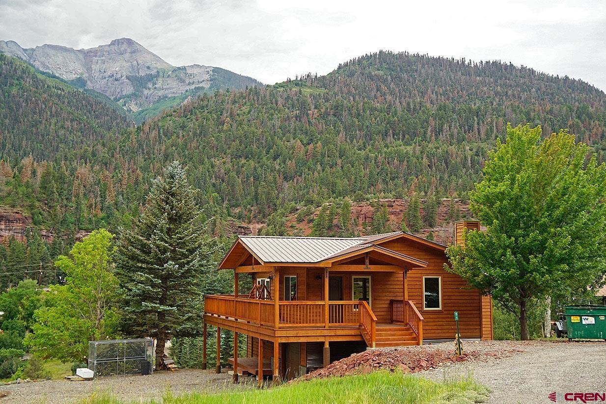 """Make your plans to come see this perfect mountain view home, perched on the benches overlooking the Ouray Valley!  It's been fully redone and is ready for you to enjoy.  It's located in the Panoramic Heights area, just north of the town of Ouray, off of County Road 14, which is the much loved road leading to Lake Lenore, the Bachelor Syracuse Mine, Baldy Mountain and other National Forest spots such as the Bridge of Heaven.  While all homes in this area offer some extra breathing room, the location of this home is especially nice.  This home has been a 'happy place' for some of the area's best known families since the time that it was built.  The current owners have done a masterful job of re-creating the home to a modern feel.  Each and every area has been redone with 4"""" farm style baseboards, new drywall, new LED lighting fixtures, new paint and new doors and hardware. Windows were replaced too-they're vinyl double pane, and there's a brand new water.  Its bright, contemporary open floorplan offers comfortable, roomy spaces. For those of you who love barn doors-you'll be in heaven-as they provide access and privacy for several spots in the home!  The main level has an especially large 14x27 great room that has a raised tile hearth with electric fireplace in its northeast corner, as well as  doors leading out to oversized decks and those tremendous views. The flooring is the extremely beautiful and durable wood-look vinyl plank.  The kitchen has been completely redone-and you'll love the 'Country Mountain' feel of the cabinetry, new butcher block counters, subway tile backsplash,  deep composite 30"""" sink and new appliances.  The large center island with quartz top situated at the view end of the kitchen is a real treat and  offers pull out shelves and soft close drawers.  This will be your perfect spot to enjoy the morning sun.  On this level are two fully redone bedrooms as well as a beautiful bathroom with custom tile shower.  Downstairs are two more bedrooms-one"""