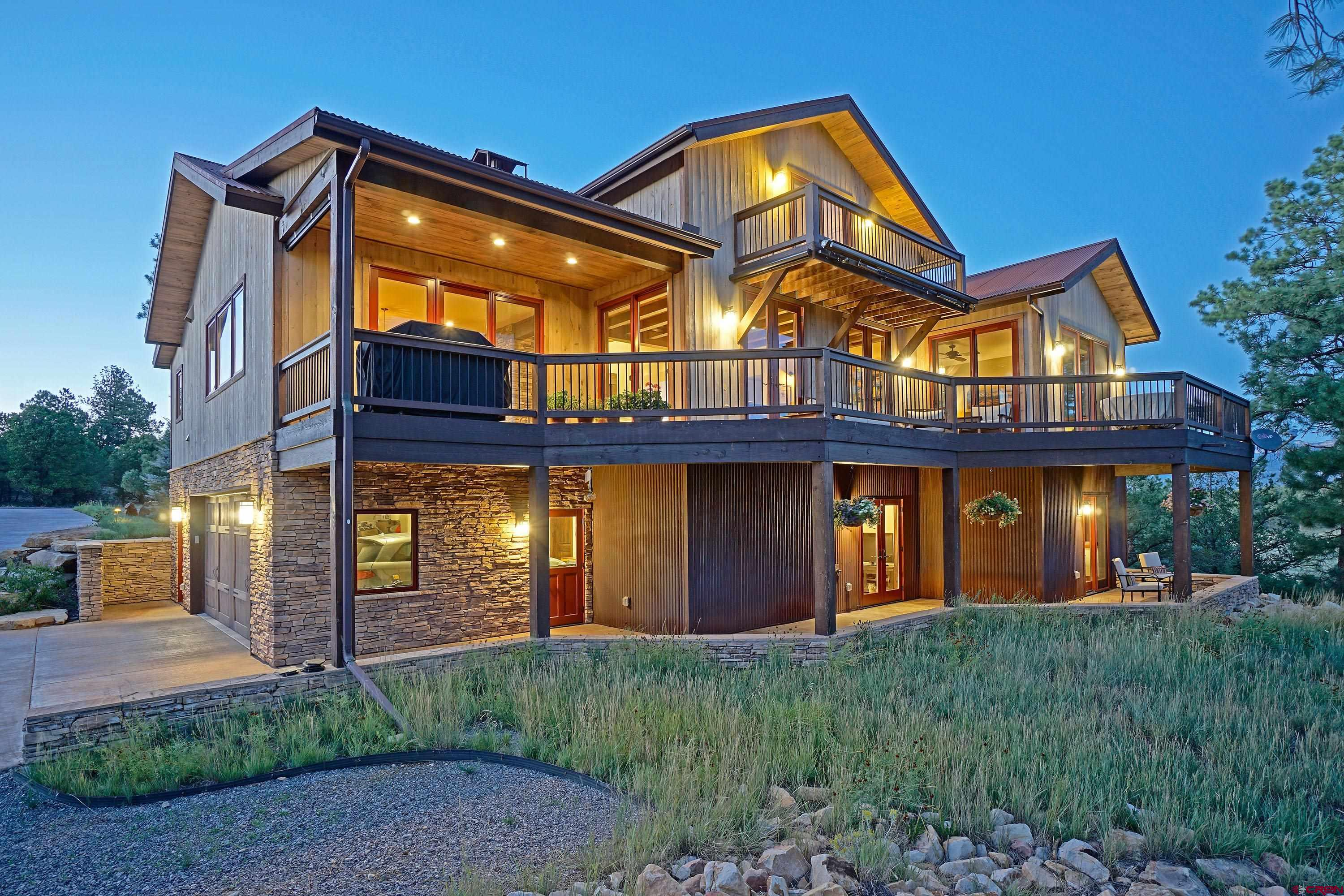 """This custom built home in Fairway Pines Estates and the Divide Ranch and Club golf course shows incredible pride of ownership and is the very definition of move-in-ready!  The property is located on a cul-de-sac and adjoins open space with a view of Mount Sneffels, the San Juans, and Cimarron mountains from the main and upper level decks.  Upon entering the home you will be amazed at the openness and very high quality finishes throughout.  In the living room there is a 2-story stone fireplace (gas) with a slate hearth, beam mantle, and forged steel fireplace doors.  Just off the living room area there is a separate formal dining area with a wall of windows/doors to take in the forest/valley views.  To the west of the living/dining rooms is the true jewel of this home which has to be seen to be believed - an enormous kitchen with some of the highest end finishes and appliances available!  When you walk into the kitchen, you'll quickly notice the stainless steel Viking 48"""" dual fuel double oven/range with a Zephyr range hood.  Next to that is the Viking refrigerator/freezer.  In the center of the kitchen is a large island with a seating area, built-in drawer-style microwave, wine refrigerator/cooler, and a custom made mahogany counter top.  The cabinetry is knotty alder with leaded glass accents and inset door/drawer fronts.  To top it off, there are granite counter tops and a slate tile backsplash with decorative accents.  The master bedroom is on the east side of the house on the main floor.  It has a large walk-in closet, great San Juan views, and a master bathroom with soaking tub, travertine tile, granite counters, and oil-rubbed bronze fixtures/lighting.  The shower is absolutely enormous with a built-in bench, decorative tile features, and multi-function shower and rain heads.  Going to the 3rd level of the house you have a large loft area that could be used for a multitude of purposes.  The loft also has it's own deck with great Cimarron views.  The lower leve"""