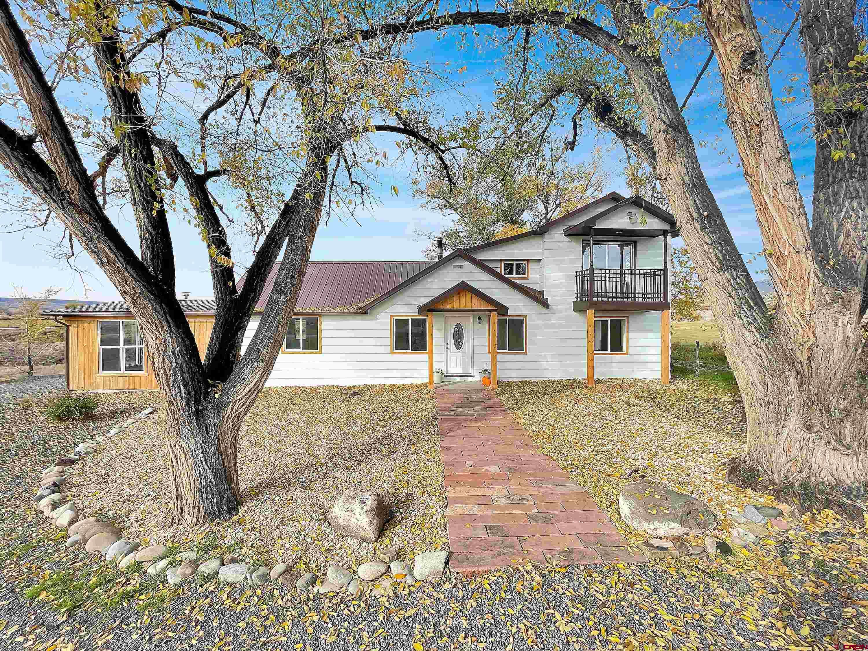 This Farmhouse Country Charmer is turn-key ready! Entire home is beautifully renovated. Property has amazing mountain/mesa views in every direction and is located minutes to Hotchkiss and Paonia. Open bright entry leads into the kitchen, dining, and family room which features a rock wall with a wood stove perfect for entertaining. 3 bedrooms on the main level including the primary suite with 2 closets and a private bath, 4th bedroom upstairs with private balcony would make a perfect home office. Additional room with its own private entrance. Relax on the deck of your private backyard listening to Cottonwood Creek at the edge of the property as it flows year round. Two sheds on concrete pads for extra storage. Additional graveled parking in the rear.  Xeriscaped front yard, inviting stone walkway, terraced garden area. Full renovation includes new black stainless kitchen appliances, farmhouse sink, quartz countertops, hot water heater, new flooring, windows, doors, all new electric heaters and upgraded electric service. Septic has been pumped and inspected. Includes highly sought after Bone Mesa water tap. High speed internet available (elevate).