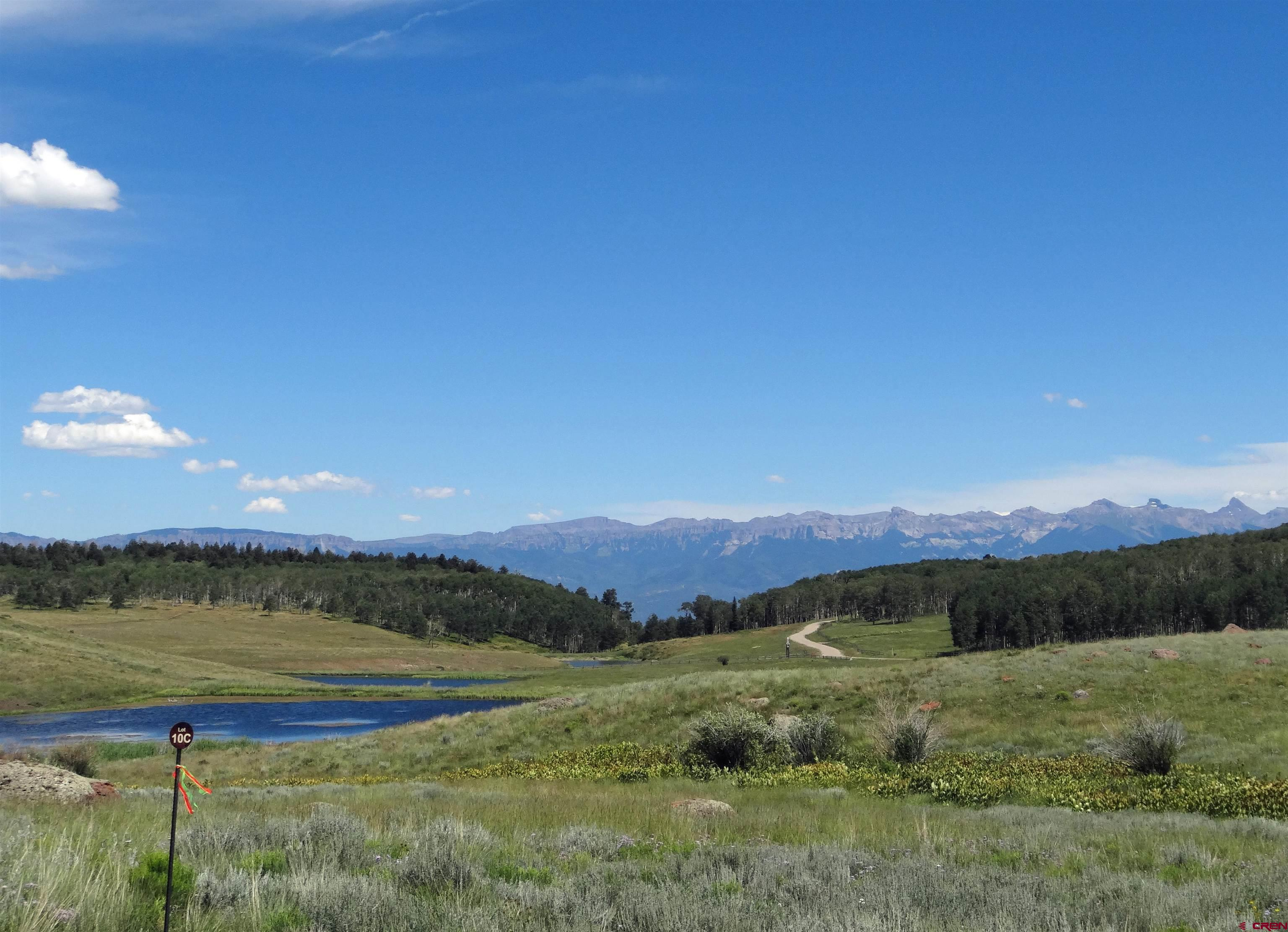 The only developer lot remaining at Spruce Mountain with a pond on site.  Build your dream home right above the water to create a Southwestern Colorado Mesa setting like no other.  A future short driveway will lead to an open building site with Cimarron Mountain range views. Stock your pond with fish and cast your day away! Private gated community within San Juan Ranch. This is a great opportunity to own a picturesque large acreage property that is just 45 minutes from Telluride and 30 minutes to Ridgway. Spruce Mountain Ranch is a private gated community within San Juan Ranch.