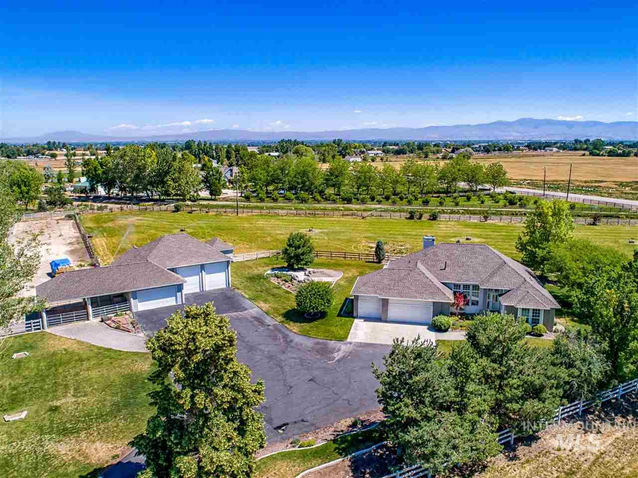 Own your own private Idaho! Views, space, privacy, beauty, fresh air, shop, RV, prime land. Superior quality custom home on 5 acres. 4 pressurized irrigated acres. Open & spacious-great for entertaining. 7 car/vehicle stalls total. 3 car attached garage + additional 2 car & 2 RV + 14X24 Office w/ shower. Hardwoods, fireplace, open kitchen design w/double ovens. Beautiful East facing backyard.  Don't miss the 3D floor plan link.