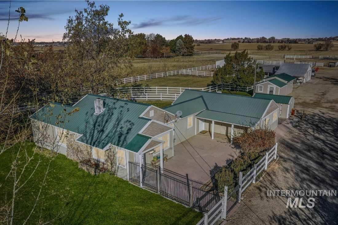 Calling all equestrians, nature lovers, and privacy seekers! Introducing this Idaho charmer that truly has it all. On nearly 5 acres of flat land, this property features two homes: an updated 1935 Ranch House 1657+ sq single story home offers 3 sizable bedrooms, 1 office and 1 bathroom, natural light, an open floor plan, and tasteful upgrades. There is a 420sqft guest quarters complete with a full bathroom, wet bar, and a bedroom with a separate entryway.     See Docs tab for additional property features.