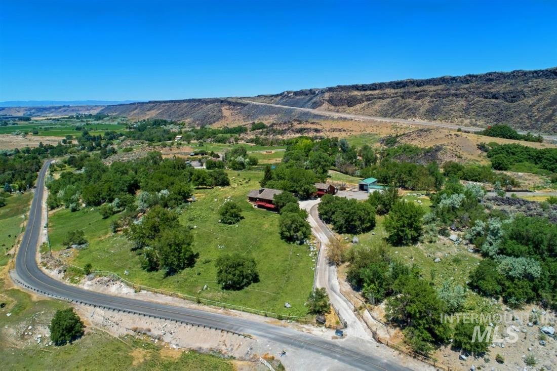 Renovated log cabin overlooking Hagerman Valley & the Snake River. It highlights a gourmet kitchen with island, granite counters, stainless appliances, & built-in double oven. Main level master showcases a vintage stove, walk-in shower, clawfoot tub & office nook. Basement includes a 2nd master & bonus room. Wrap around porch has a hot tub, picnic table, & bench seating. Exterior includes a 3 bay garage with guest apartment, 3 horse stall outbuilding with tack room, corrals, & equipment shed with a RV bay.
