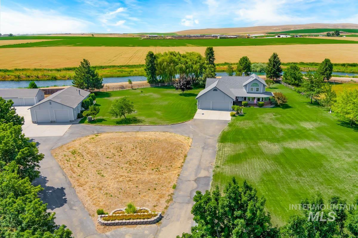 3bed/3bath home on park-like setting with 75 mature shade trees, oversized 3car garage on 6+ acres. Two irrigated pastures for horses. Half mile S of Kuna-12 minutes to freeway. Two very large shops (one insulated) perfect for light industrial or home-based business with an additional living quarters; room to park trucks (even semis)–no CCRs. RV storage income possible. Open floor-plan home with large office, storage, built-ins & circular staircase that overlooks the great room. - Kelly D Kitchens, Voice: 208-794-7863, Keller Williams Realty Boise, Main: 208-672-9000, http://www.KellyKitchensRealty.com