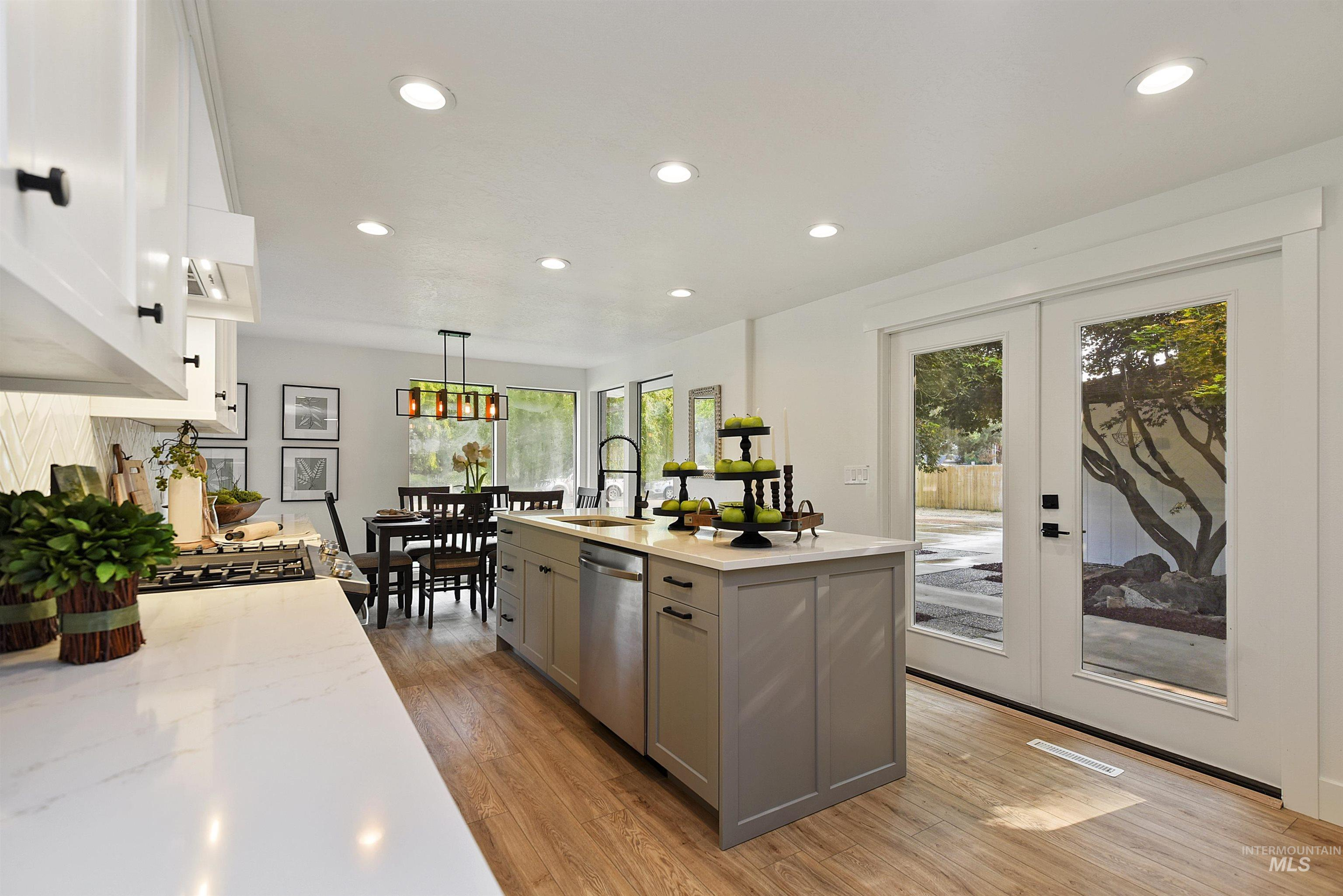 This renovation is electric! Gourmet kitchen with quartz counters, impressive tile work, gas range & expansive island. Custom cabinetry throughout includes soft close uppers & lowers, pull out shelves/bins & a gorgeous wooden hood vent. Main level features large windows, a gas fireplace & the kitchen of your dreams! Upstairs you'll get lost in the master suite with it's own sitting room & balcony overlooking your huge half acre lot. Don't miss the walk-in shower & large closet! Two additional bedrooms & bathroom complete the upstairs. Entertain in the lower level with awesome recreational space where you can walk out to an impressive covered patio. You'll also find an additional bedroom or office with it's own gas fireplace. Downstairs has a light & bright laundry room, storage & full bathroom. There's room for it all with a full half acre, extra concrete, an oversized two car garage & space for your RV on this fully fenced lot without HOA's. Hurry because you don't want to miss the one with the green door! - Ruth Kmiecik, Main: 208-965-3570, Peterson & Associates REALTORS, Main: 208-466-4098,
