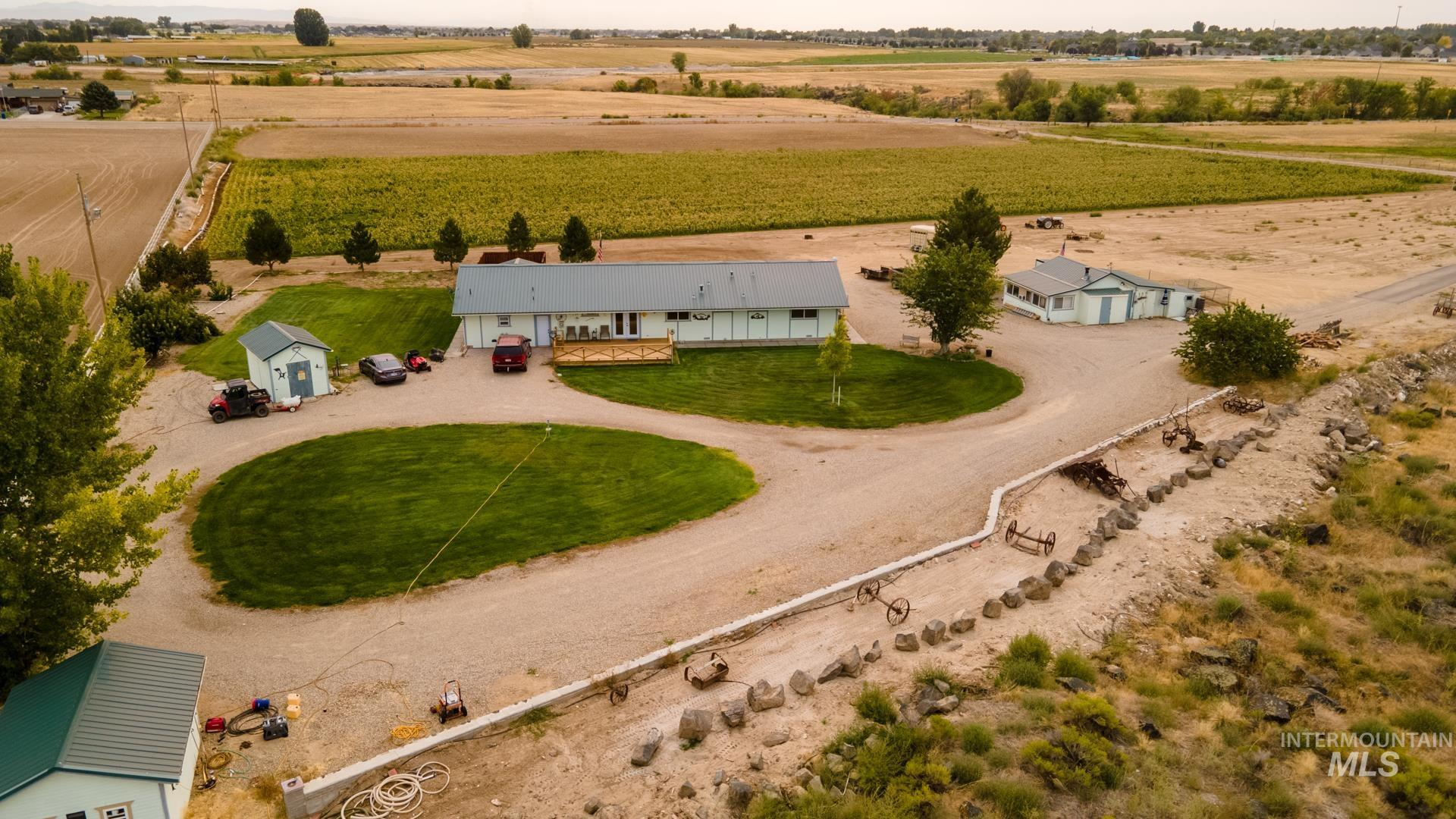 Great opportunity to own this unique acreage property with a custom single level home. 2 master bedrooms, huge walk in closet, 4Bedroom 3 Bathroom 2080 square foot home located in Kuna on 10 irrigatable acres currently planted in Corn and alfalfa seed.  20x23 wood shop finished with electrical and wood stove. 2 extra storage sheds with concrete floors. 5x48 Sunroom. Bring your cows, horses, toys, etc. Full RV hook ups, cold storage room for hanging meat. New metal roof, new vinyl fencing, enclosed gazebo, full sprinkler system, etc. Close to everything. No CC&R's fruit trees, low maintenance landscaping.. a must see for anyone seeking country living! Listing agent is related to seller - Lini K Chytka, Voice: 208-249-0671, Boise Premier Real Estate, Main: 888-506-2234,